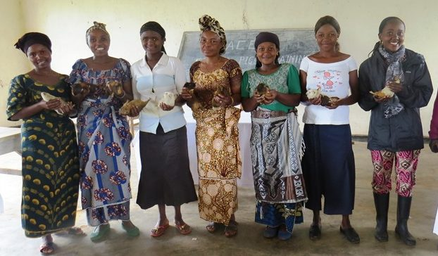 Women from GRACE's training stand in a row holding guinea pigs.
