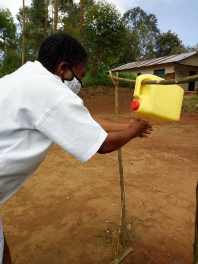 A child wearing a mask uses a no-touch hand washing station.
