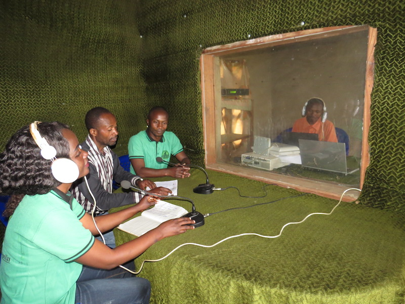 GRACE Educators speak into microphones at the radio station.