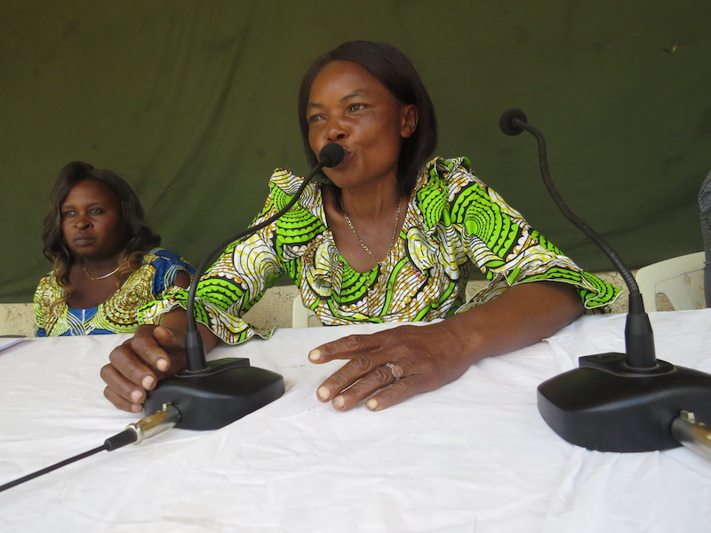 GRACE staff speak into a microphone at International Women's Day.